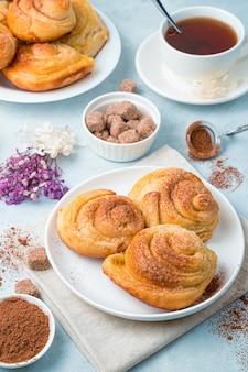 Frische schneckenbrötchen mit zimt, kakao und einer tasse tee auf einem zarten blauen hintergrund.