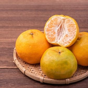 Frische, schöne orangefarbene mandarine auf bambussieb über dunklem holztisch. saisonale, traditionelle frucht des chinesischen neujahrsfests, nahaufnahme.