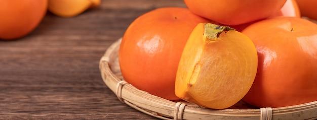Frische, schöne orangefarbene persimone kaki auf bambussieb über dunklem holztisch. saisonale, traditionelle frucht des chinesischen neujahrsfests, nahaufnahme.