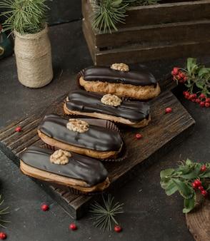 Frische schokoladen-eclairs mit walnuss auf holzbrett