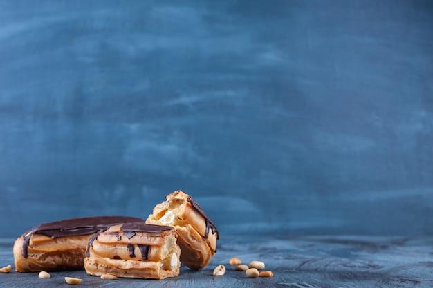 Frische schokoladen-eclairs und erdnüsse auf blau gelegt.