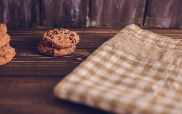 Frische schokoladensplitterplätzchen, frisch gebacken auf rustikalem holztisch. tiefenschärfe. kopieren sie platz.