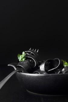 Frische schwarze nudeln auf gabel