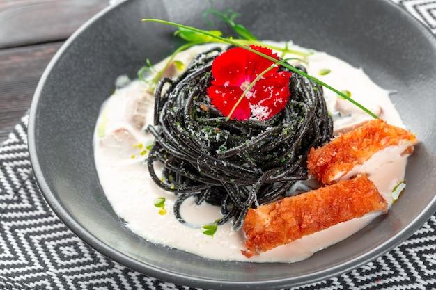 Frische schwarze taglioliniteigwaren mit huhn in den kräutern auf rucola und tomaten