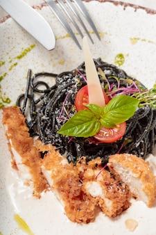 Frische schwarze taglioliniteigwaren mit huhn in den kräutern