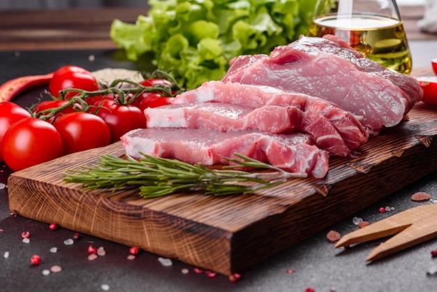 Frische schweinefleischstücke bereit, in der küche zu kochen. lendenmedaillons steaks in einer reihe bereit zu kochen
