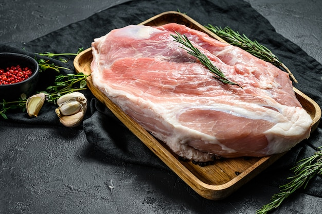 Frische schweinefleischstücke. rohes fleisch mit gewürzen. hinterbeinsteak. schwarzer hintergrund. ansicht von oben