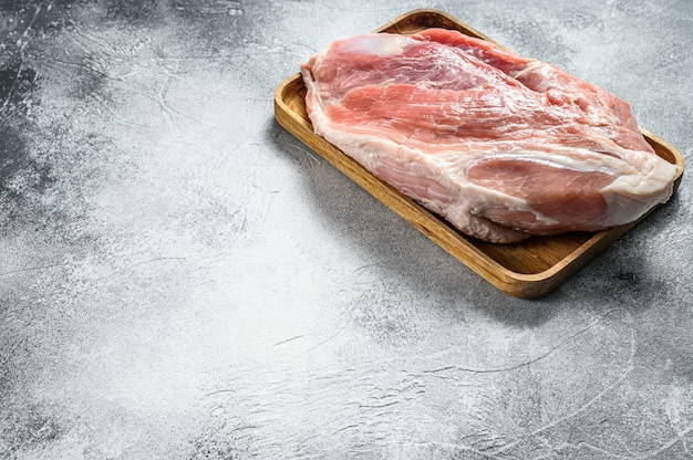 Frische schweinefleischstücke. rohes fleisch mit gewürzen. schulterkolbenteil. grauer hintergrund. ansicht von oben