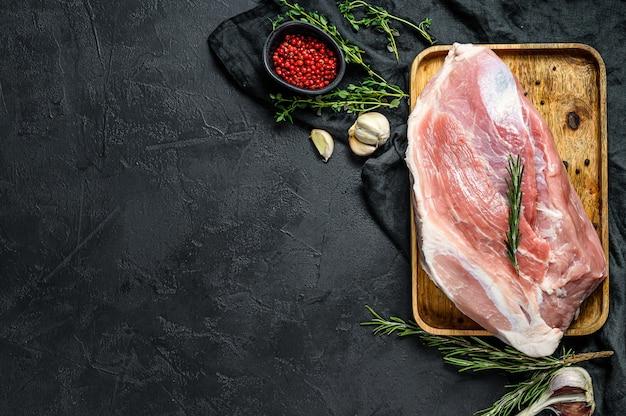 Frische schweinefleischstücke. rohes fleisch mit gewürzen. schwarzer hintergrund. ansicht von oben
