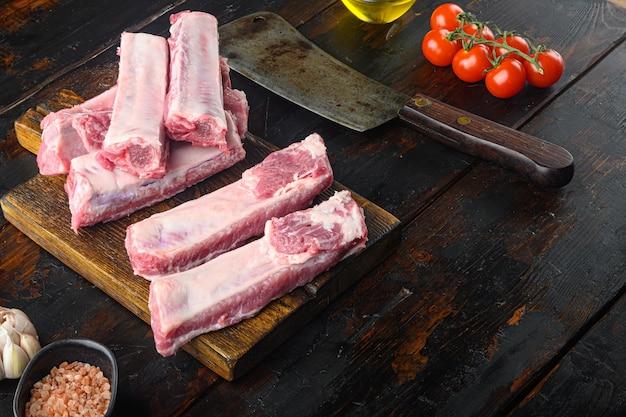 Frische schweinerippchen mit rosmarinset, mit altem fleischbeilmesser, auf altem dunklem holztisch