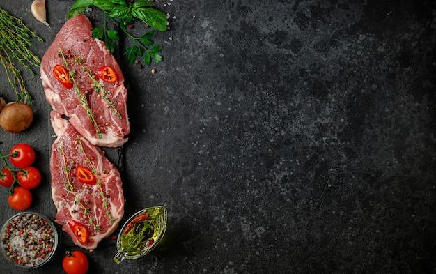 Frische schweinesteaks mit paprika, kräutern und gemüse. draufsicht, kopierraum. italienische küche