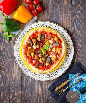 Frische selbst gemachte pizza mit unterschiedlichem gemüse auf einem holztisch