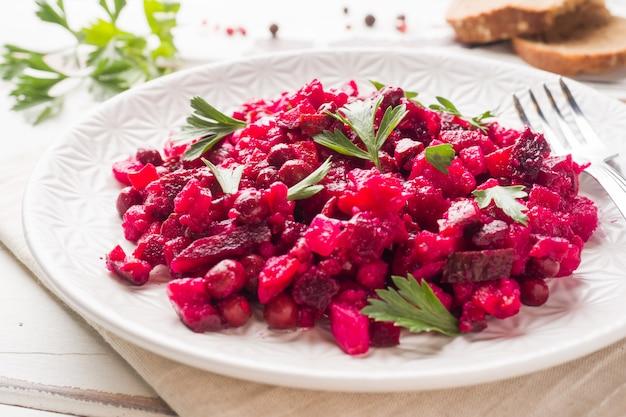 Frische selbst gemachte rote-bete-wurzeln salat essigsoße in einer weißen schüssel. traditionelles russisches essen. kopieren sie platz