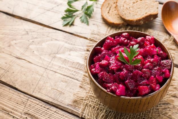 Frische selbst gemachte salatessigsoße der roten rübe in einer hölzernen schüssel. traditionelles russisches essen.