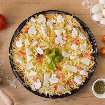 Frische selbst gemachte ungekochte pizza mit bestandteilen auf backblech