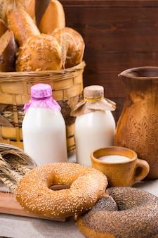 Frische sesambagels und milch für ein gesundes frühstück, serviert in glasflaschen mit einem rustikalen korb mit verschiedenem brot dahinter