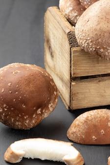 Frische shiitake-pilze in der box und auf dem tisch.