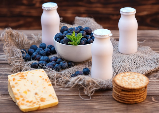 Frische sommerblaubeere mit blatt in der weißen schüssel, joghurtflaschen auf dem braunen hölzernen hintergrund