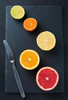 Frische sortierte zitrusfrüchte auf dunklem hintergrund mit kopienraum. draufsicht. selektiver fokus.
