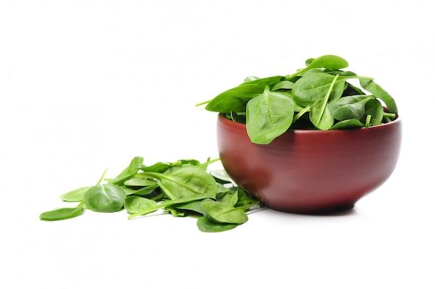 Frische spinatblätter in der schüssel isoliert