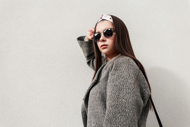 Frische städtische porträtfrau in modischer sonnenbrille in vintage-bandana in stilvollem mantel an einem sonnigen tag in der nähe der weißen wand. attraktives mädchen in schönen trendigen kleidern genießt die frühlingssonne in der stadt. stil.