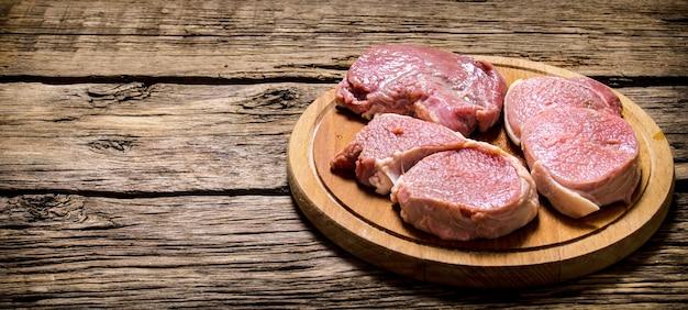 Frische steaks auf einem alten holzbrett auf hölzernem hintergrund