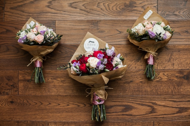 Frische stilvolle rosen, die blumensträuße auf hölzernem hintergrund heiraten