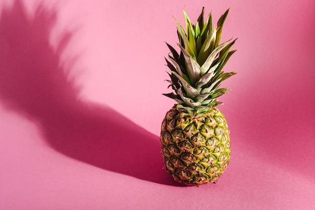 Frische süße ananas auf rosa oberfläche