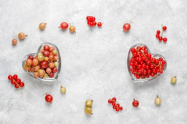 Frische süße bio-stachelbeeren und rote johannisbeeren in schalen