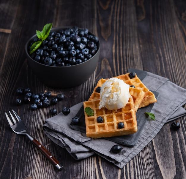 Frische süße blaubeere mit aromatischen belgischen waffeln vanilleeis und honig dunklem holztisch