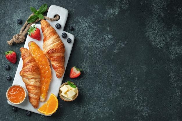 Frische süße croissants mit butter und orangenmarmelade zum frühstück. kontinentales frühstück. ansicht von oben. flach liegen.