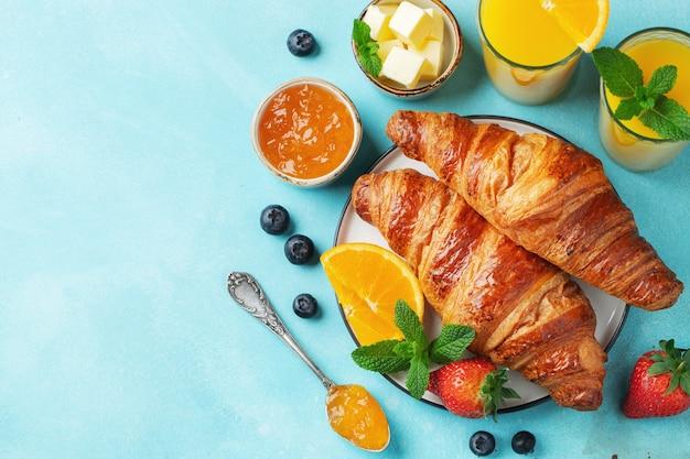 Frische süße croissants mit butter und orangenmarmelade zum frühstück. kontinentales frühstück auf einem hellen betontisch. ansicht von oben. flach liegen.