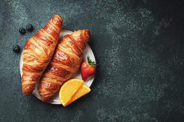 Frische süße croissants mit butter und orangenmarmelade zum frühstück. kontinentales frühstück auf einem schwarzen betontisch. ansicht von oben. flach liegen.