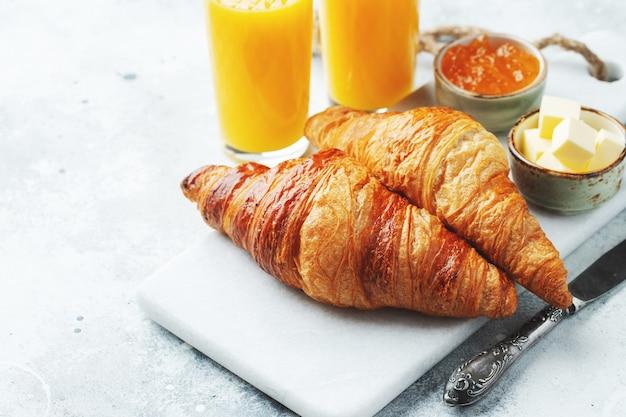 Frische süße croissants mit butter und orangenmarmelade zum frühstück. kontinentales frühstück auf einem weißen betontisch.