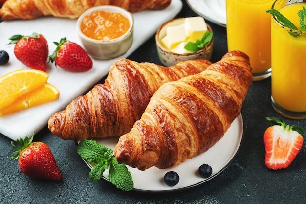Frische süße croissants mit butter und orangenmarmelade zum frühstück. kontinentales frühstück.