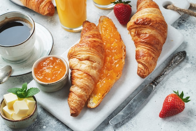 Frische süße croissants mit butter und orangenmarmelade zum frühstück.
