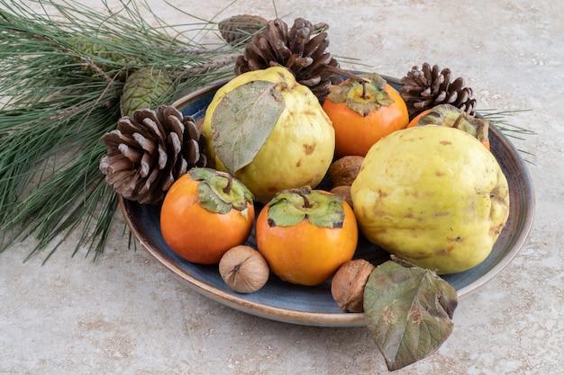 Frische süße früchte mit nüssen und tannenzapfen