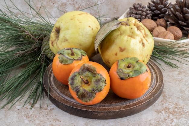 Frische süße früchte mit nüssen und tannenzapfen Kostenlose Fotos