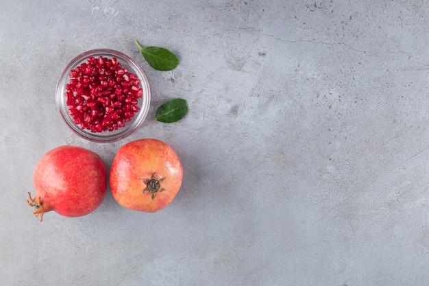 Frische süße granatäpfel mit blättern auf steinhintergrund.