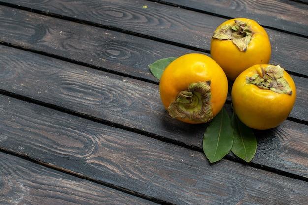 Frische süße kakis der vorderansicht auf hölzernem rustikalem schreibtischfrucht-reifem weichem
