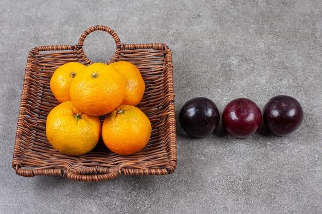 Frische süße mandarinen mit pflaumen auf einem weidenkorb