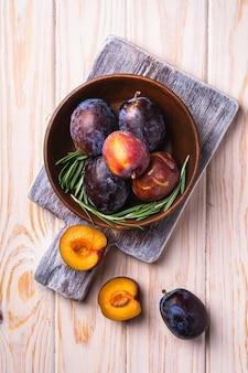 Frische süße pflaumenfrüchte ganz und in braune holzschale mit rosmarinblättern auf altem schneidebrett, holztischhintergrund, draufsicht geschnitten