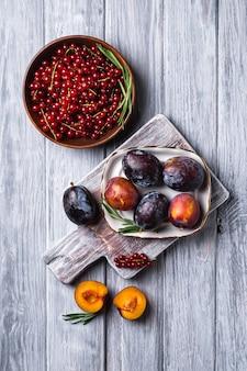 Frische süße pflaumenfrüchte ganz und in teller geschnitten mit rosmarinblättern auf altem schneidebrett mit roten johannisbeeren in holzschale