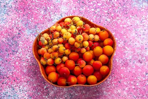 Frische süßkirschen mit halber draufsicht mit pflaumen im teller auf rosa schreibtisch.