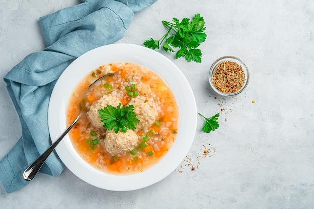 Frische suppe mit fleischbällchen und frischem grün auf grauem hintergrund. ansicht von oben, kopienraum.