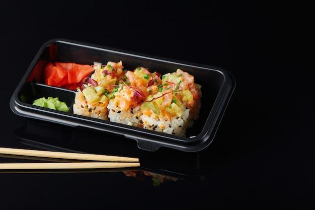 Frische sushi-rollen mit garnelen, krabben in lunchbox zum mitnehmen. gehen sie japanisches sushi-food-konzept für ein gesundes mittagessen. detailansicht auf schwarzem hintergrund.