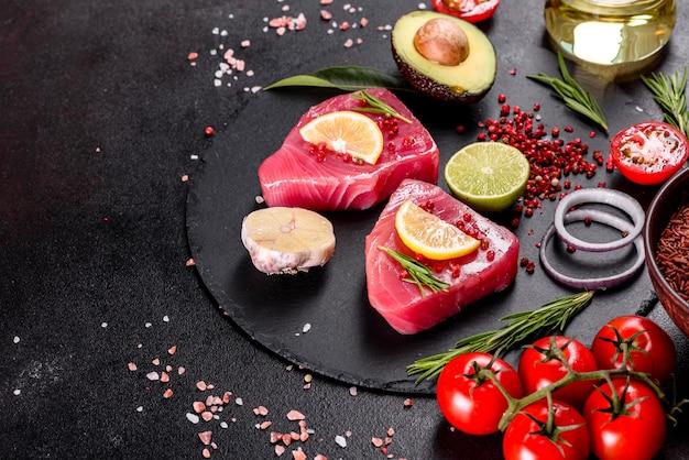 Frische thunfischfiletsteaks mit gewürzen und kräutern auf einem schwarzen tisch