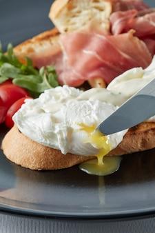 Frische toastsandwiches mit pochiertem ei, tomate, salat und speck auf teller, messer, das ein ei schneidet