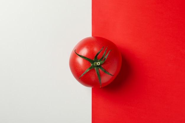Frische tomate auf zweifarbigem hintergrund, draufsicht