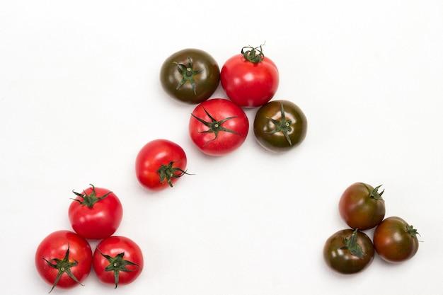 Frische tomaten auf dem tisch. weißer hintergrund. platz kopieren. flach legen